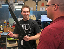 staff member demonstrates a shotgun
